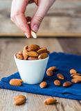 Eat nuts, almonds hands of white cup Stock Photos
