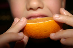 Eat an Orange. Boy eating orange segment royalty free stock photography