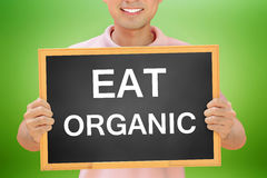 EAT ORGANIC text on blackboard held by smiling man Royalty Free Stock Photography