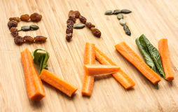 Eat raw concept with vegetables and seeds. Eat raw concept with carrots, spinach, raisins and pumpkin seeds stock photography