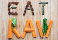 Eat raw concept with vegetables and seeds. Eat raw concept with carrots, spinach, raisins and pumpkin seeds stock photo