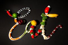 Eat sign spelled with healthy fruits and vegetables royalty free stock photo