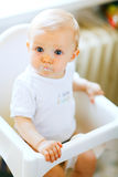 Eat smeared baby in chair impressively looking Royalty Free Stock Photo