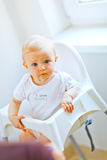 Eat smeared baby in chair interestedly looking Stock Image