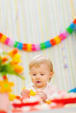 Eat smeared baby eating orange at birthday party Stock Photos