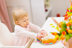 Eat smeared baby touched birthday cake by hands Stock Images