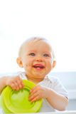 Eat smeared smiling baby girl playing with plate Royalty Free Stock Photography