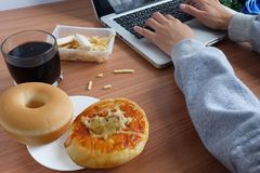 Eat snacks with Donut bread, Pizza and cola water drink during work with laptop stock photo