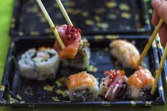 Eat sushi with chopsticks at the same time. People Eating sushi with chopsticks at the same time royalty free stock images