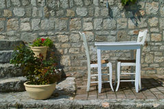 Eat and trink in nature. Two chairs and a table invites for food or drink Royalty Free Stock Photo