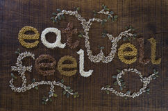 Eat Well, Be Well written and decorated in seeds. The phrase 'Eat Well, Be Well', decoratively written in sesame seeds, sunflower seeds, flax seeds, alfafa seeds Stock Image