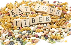 Eat your fiber. Assorted beans and whote wheat pasta mound with the words eat your fiber on wooden blocks placed on top Royalty Free Stock Images
