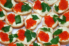 Eatable background of red caviare sandwiches. Decorated with green leaves of parsley Royalty Free Stock Photography