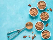 Eatable raw monster cookie dough. Safe-to-eat raw monster cookie dough in small portion bowl, ice cream scoop and nuts on blue background. Ideas and recipes for Royalty Free Stock Photos