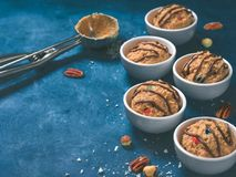 Eatable raw monster cookie dough. Safe-to-eat raw monster cookie dough in small portion bowl, ice cream scoop and nuts on blue background. Ideas and recipes for Stock Photos