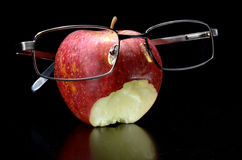 Eaten apple with glasses Royalty Free Stock Photos