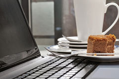 Eaten cake on laptop beside stack of dirty plates on desk Stock Photo