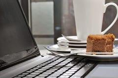 Eaten cake on laptop beside stack of dirty plates on desk Stock Photo