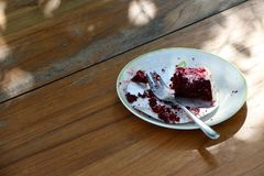 Eaten cake in the white plate with small spoon on the wooden table. An item of soft, sweet food made from a mixture of flour, shortening, eggs, sugar, and Royalty Free Stock Photo