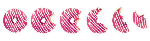 Eaten donut with pink icing and white stripes. Isolated on white background. Top view Stock Photography