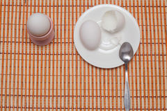 Eaten egg. Eggshell, egg and spoon on a white plate Royalty Free Stock Photo