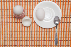 Eaten egg. Eggshell, egg and spoon on a white plate Royalty Free Stock Images
