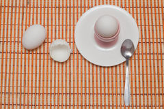 Eaten egg. Eggshell, egg and spoon on a white plate Stock Photography