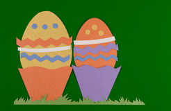 Eater eggs. Colorful eggs with grass and cut on paper, easter egg on a green background stock images
