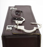 Eather suitcase from pinned open handcuffs Stock Photo
