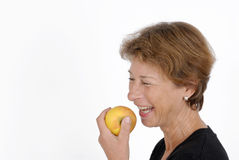 Eating. Older woman with an apple Royalty Free Stock Photography
