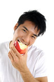 Eating. Young Asian man eating red apple close up Stock Photos