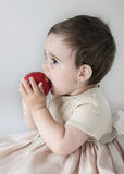 Eating apple. Little girl in a pink dress sitting, eating apple Royalty Free Stock Photography