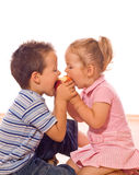 Eating an apple. Little boy and girl bite an apple stock photo