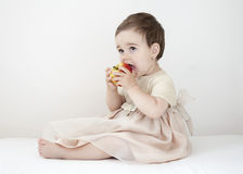 Eating apple. Little girl in a pink dress sitting, eating apple; white background Royalty Free Stock Image