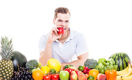 Eating an apple from stack of fruit and vegetables Royalty Free Stock Photography