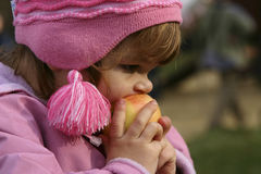 Eating apple. Child eating an apple outdoors Royalty Free Stock Photos