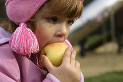 Eating apples. Child eating an apple outdoors Royalty Free Stock Photography