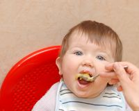 Eating baby. Beautiful baby, eating the porridge Stock Images