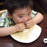 Eating baby. To grab pasta Stock Photos