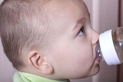 Eating baby. Portrait of nice eating blue-eyed baby close up Royalty Free Stock Images