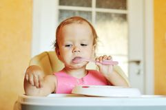 Eating baby girl. Funny eating baby girl with dirty face Stock Photo