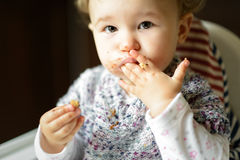 Eating baby girl with messy face Royalty Free Stock Photo
