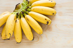 Eating Bananas. Ripe bananas on wood table that was ate some piece Stock Image