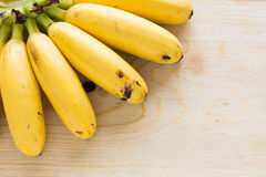 Eating Bananas. Ripe bananas on wood table that was ate some piece Royalty Free Stock Photography