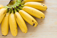 Eating Bananas. Ripe bananas on wood table that was ate some piece Royalty Free Stock Photos