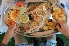 Eating on the beach. Eating Grilled turbot Royalty Free Stock Photography