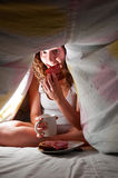 Eating at bed. Woman is sitting under cover in bed and eating Stock Photo