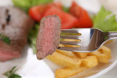 Eating beef steak meat with fork Stock Photos