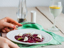 Eating beet salad with goat cheese, garlic and sesame, hands Stock Photos