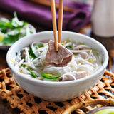 Eating a bowl of pho with chopsticks and picking up beef Royalty Free Stock Image
